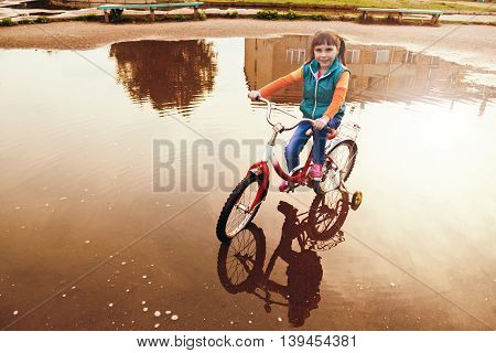 Young girl is cycling rides through a puddle in the park.