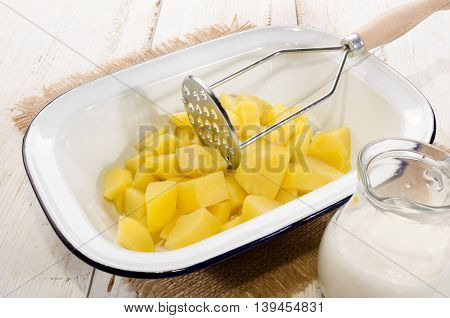 potato cubes in a enamel bowl and milk to make mashed potatoes