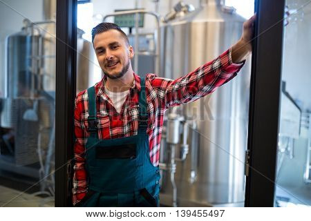 Happy brewer standing at brewery