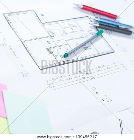 Pens and professional architectural drawings on paper