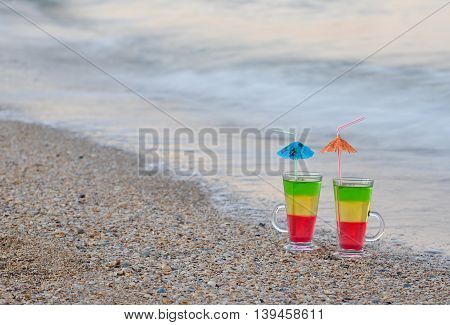 Two cocktails with straws in the sand on the seashore space for text