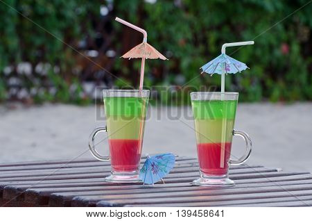 Two glasses with colored cocktails and straws on a wooden deck chair in the backyard