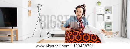 Shot of a young woman sitting on a pouf and listening to music