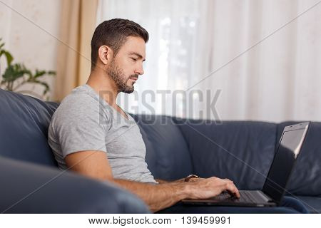 Young tired casual man sleep at laptop indoor
