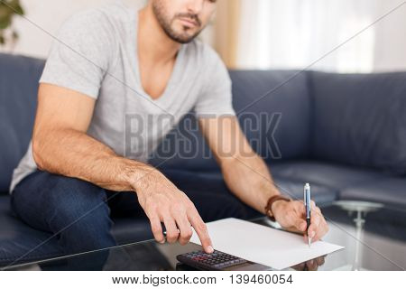 Young casual man calculating on desk black paper and calculator