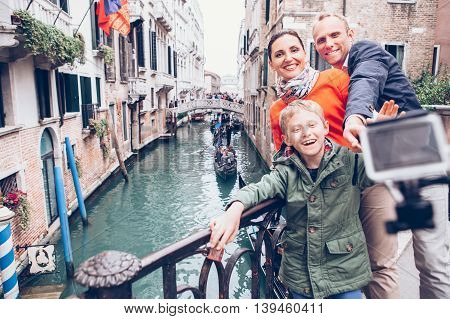 Happy family take a self photo on the bridge over Venecian channel