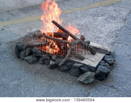 Burning logs in tray in advance of Midsummer night fire jumping in Spain