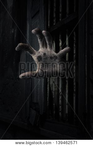 Zombie hand rising out from the old window ancient house Halloween concept