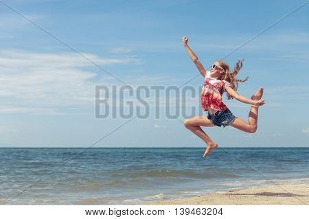 Happy teen girl jumping on the beach at the day time. One teenager having fun on the nature. Concept of happiness.