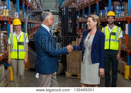 Focus of business people are handshaking in front of workers in a warehouse