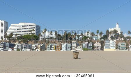 deserted, wide beach of Santa Monica in the metropolitan area of Los Angeles, California, houses, holiday apartments, palm trees and bright blue sky
