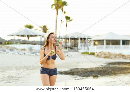 Young brunette girl blowing soap bubbles on the seashore
