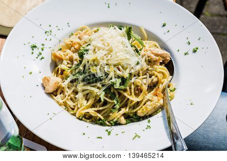 Spaghetti bolognese. Plate of Italian spaghetti spinach chicken and Parmesan cheese.