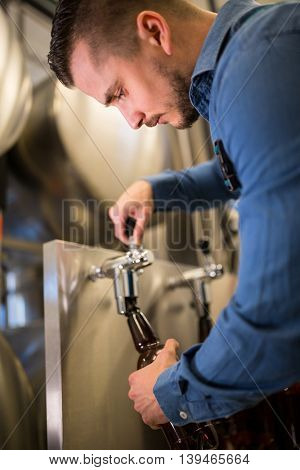 Close-up of brewer filling beer in bottle from tank at brewery