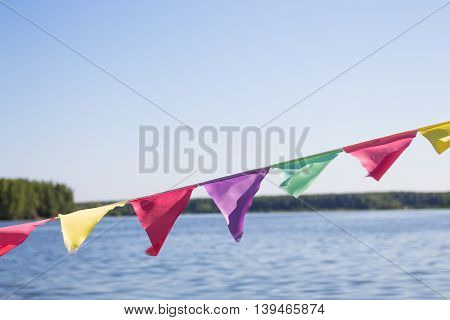 Multi-colored flags fluttering in the background of a large lake