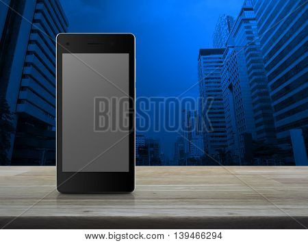 Modern smart phone with blank grey screen on wooden table over city tower background