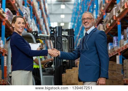Business people are handshaking and looking the camera in front of workers in a warehouse