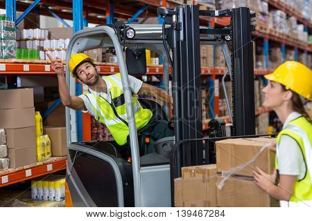 Focus of worker sitting on a pallet truck is pointing shelves in a warehouse