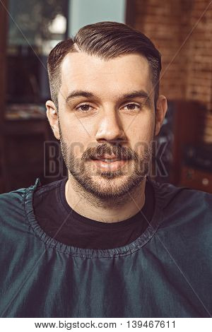 The young man with a beard and mustache looking at camera in barbershop