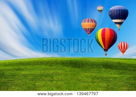 Colourful hot air balloons flying over green field and blue sky.