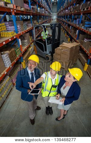 High angle view of worker showing shelves to managers in a warehouse