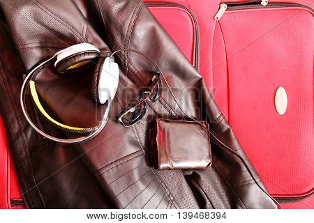 Ready to travel. A suitcase with glasses wallet and a leather jacket.