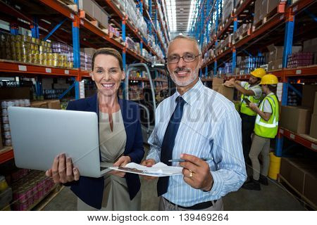 Businessmen using laptop and writing on paper in warehouse