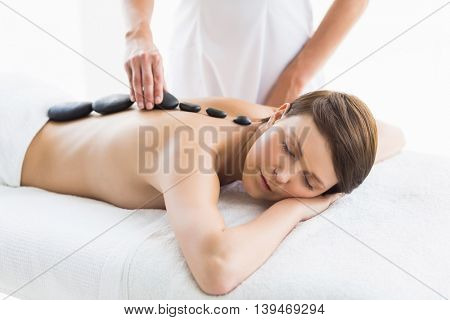 Beautiful woman receiving hot stone massage from masseuse at spa
