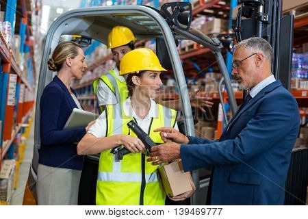 Businessman controlling digital device of worker in warehouse