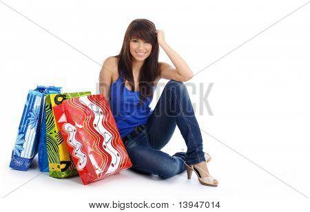 tiro isolado de uma mulher feliz com sacos de compras no chão