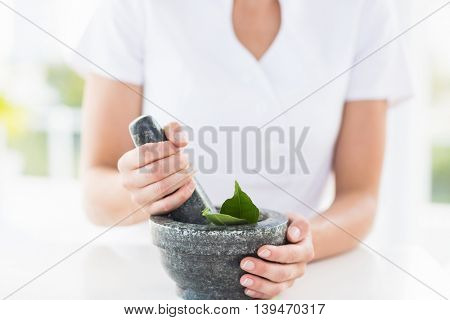 Midsection of woman holding mortar and pestle on table at home