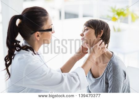 Doctor examining female patient at clinic
