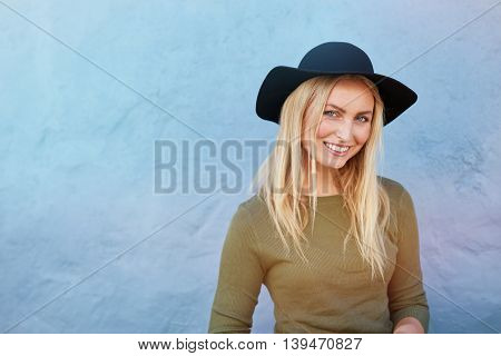 Beautiful Smiling Woman Posing By Blue Wall