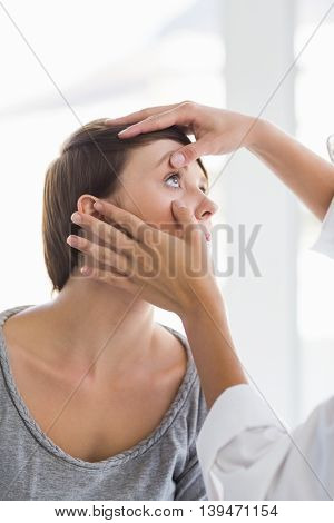 Cropped image of doctor checking woman eye at clinic
