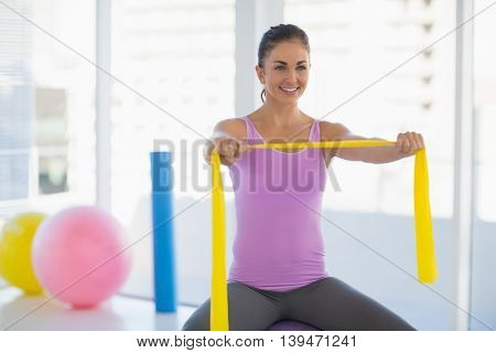Happy woman exercising with resistance band at fitness studio