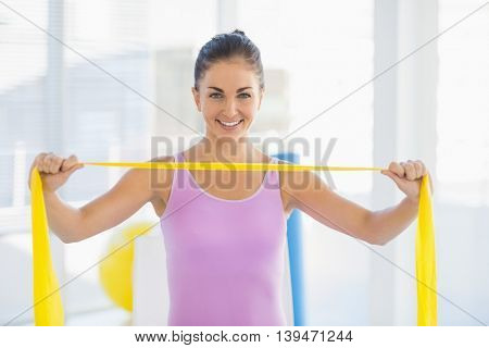 Portrait of smiling woman holding resistance band at fitness studio