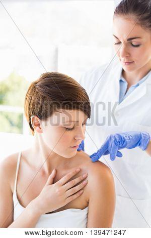 Doctor examining beautiful woman at clinic