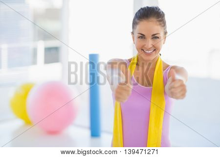 Portrait of smiling happy woman with resistance band at fitness studio