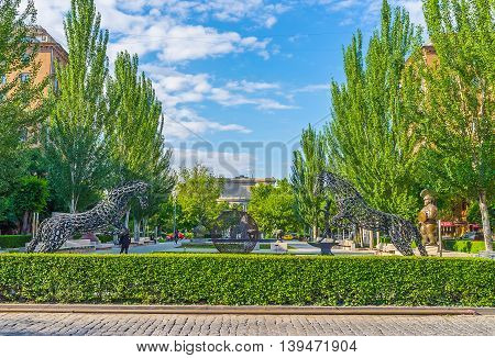 YEREVAN ARMENIA - MAY 29 2016: The sculpture of jumping horses made of the horseshoes in the sculpture garden at Tamanyan street on May 29 in Yerevan.