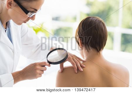 Doctor examining woman back with magnifying glass at clinic