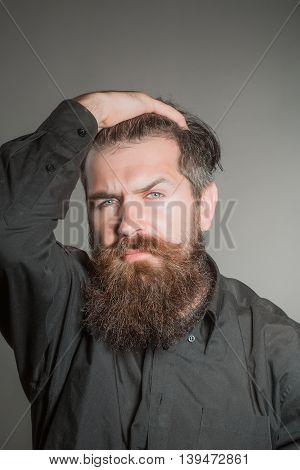 handsome bearded young man hipster with long beard and mustache in black shirt and serious face in studio on grey background