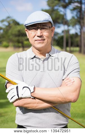 Portrait of happy golfer with arms crossed while standing at golf course