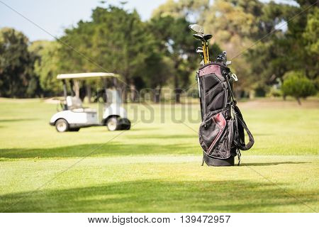 Filled golf bag and golf buggy on field