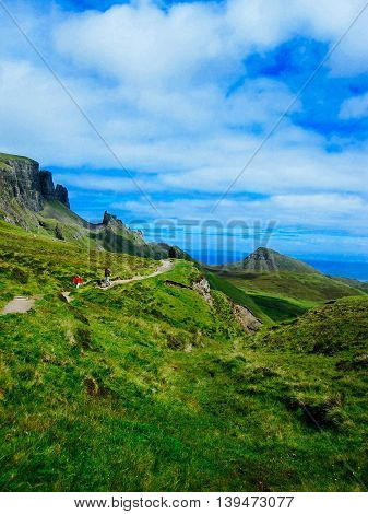 ISLE OF SKYE UNITED KINGDOM - JULY 25 2011: A view of tourists hiking up a path among the rolling green hills on the Isle of Skye in Scotland.