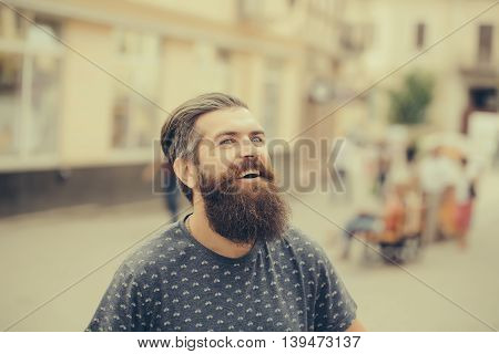 handsome sexy bearded young man hipster with long beard and mustache has stylish hair on smiling hairy face outdoor closeup