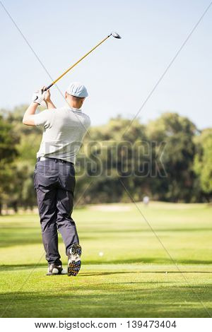 Rear view of golf player taking shot