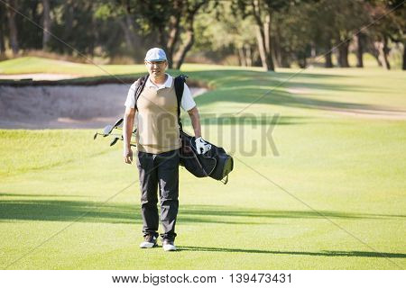 Sportsman walking with his golf bag on a field