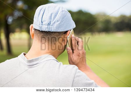 Rear view of golfer calling with his mobile phone