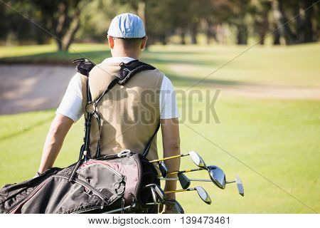 Rear view of sportsman holding a golf bag on a field