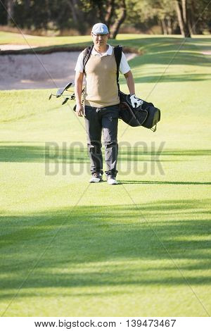Portrait of sportsman walking with his golf bag on a field